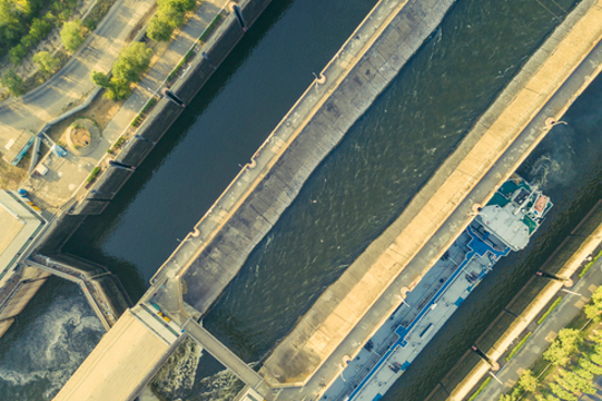 aerial-drone-shot-river-gateway-structure-barge-cargo-ships-f